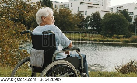Senior Disabled Woman Sitting In The Wheelchair Enjoying Autumn Breeze Near The River. High Quality