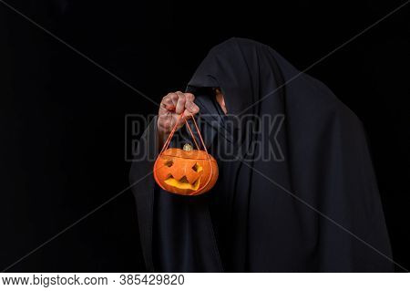 Man In Black Clothes Holds Jack-o-lantern, Lantern Glows With Yellow Light Isolated On Black Backgro