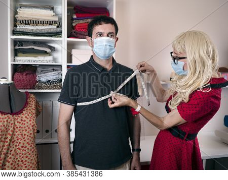 Caucasian Man And Woman Wearing Surgical Mask In A Dressmaker Workshop