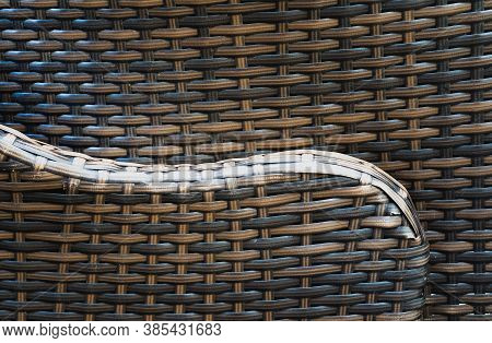 A Graceful Line Of The Arm Of A Rattan Chair With Embossed Texture Against The Background Of Another