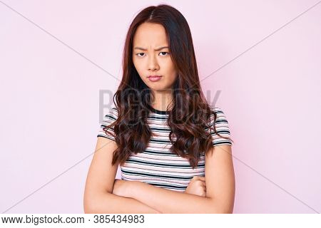 Young beautiful chinese girl wearing casual clothes skeptic and nervous, disapproving expression on face with crossed arms. negative person.
