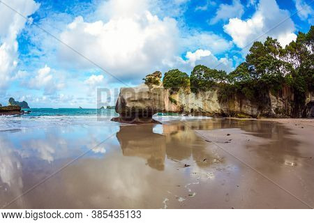 Cathedral Cave on the North Island of New Zealand. Coromandel Peninsula. Bizarre clouds and coastal cliffs reflected in the tidal waters of the Pacific Ocean. The concept of ecological, photo tourism