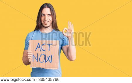 Young adult man with long hair holding act now banner doing ok sign with fingers, smiling friendly gesturing excellent symbol