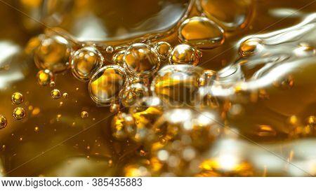 Macro shot of Splashing Oil on Golden Background