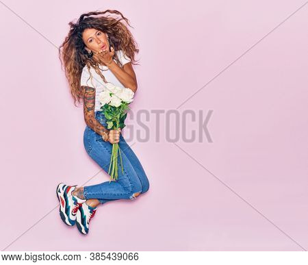 Young beautiful curly woman with tattoo holding bouquet of white rose smiling happy. Jumping with smile on face throwing kiss with hand over isolated pink background