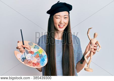 Young chinese woman wearing artist look with beret holding manikin winking looking at the camera with sexy expression, cheerful and happy face.