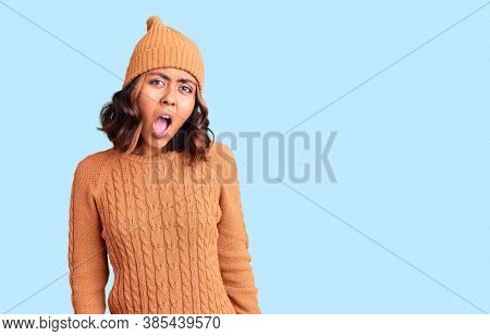 Young beautiful mixed race woman wearing wool sweater and winter hat in shock face, looking skeptical and sarcastic, surprised with open mouth
