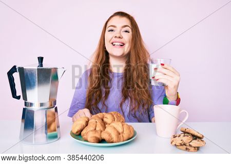 Young redhead woman eating breakfast skeptic and nervous, disapproving expression on face with crossed arms. negative person.