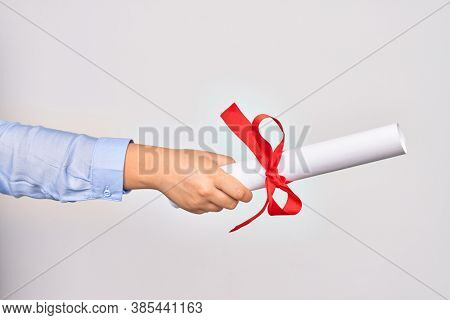 Hand of caucasian young woman holding graduated diploma degree over isolated white background