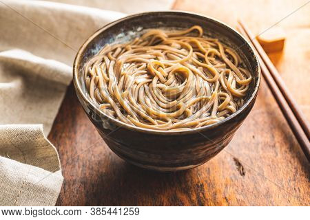 Cooked soba noodles. Traditional asian pasta in bowl on wooden table.