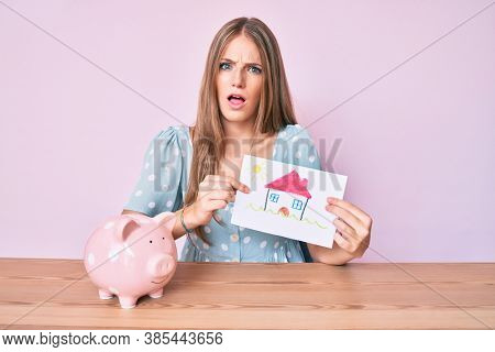 Young blonde woman holding house draw and piggy bank in shock face, looking skeptical and sarcastic, surprised with open mouth