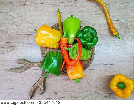 Bulgarian Pepper Is Green, Red And Yellow On A Wooden Cutting Board On The Work Surface.