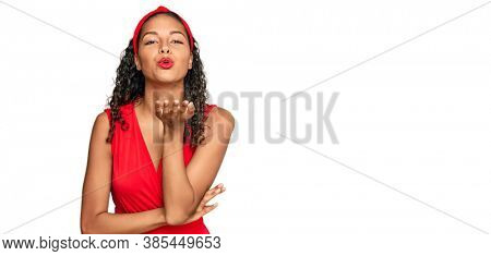 Young african american girl wearing elegant and sexy look looking at the camera blowing a kiss with hand on air being lovely and sexy. love expression.