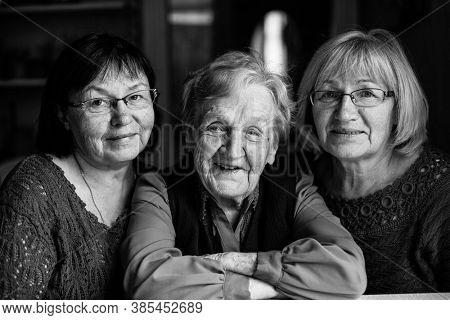 An old woman with two adult daughters. Black and white photography.