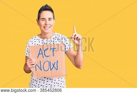 Young woman with short hair holding act now banner surprised with an idea or question pointing finger with happy face, number one