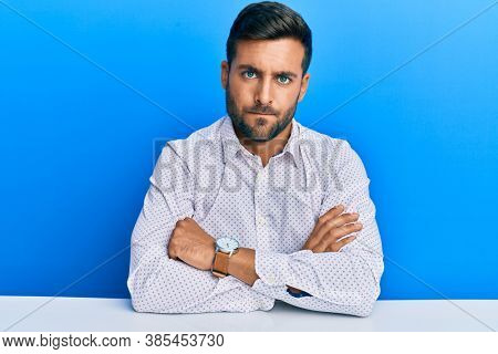 Handsome hispanic man wearing business clothes sitting on the table skeptic and nervous, disapproving expression on face with crossed arms. negative person.