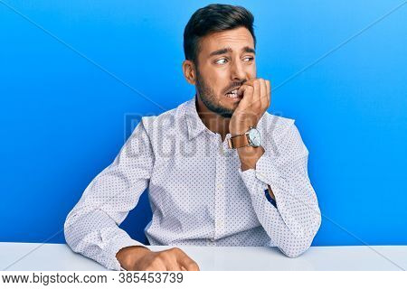 Handsome hispanic man wearing business clothes sitting on the table looking stressed and nervous with hands on mouth biting nails. anxiety problem.