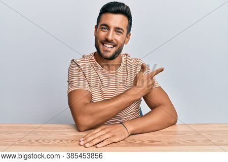 Handsome hispanic man wearing casual clothes sitting on the table cheerful with a smile of face pointing with hand and finger up to the side with happy and natural expression on face