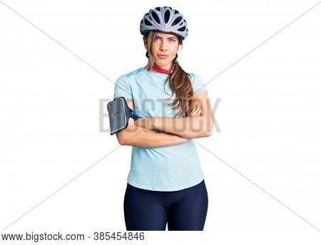 Beautiful caucasian young woman wearing bike helmet skeptic and nervous, disapproving expression on face with crossed arms. negative person.