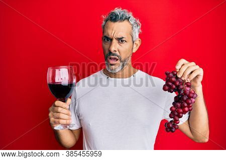 Middle age grey-haired man holding branch of fresh grapes and red wine in shock face, looking skeptical and sarcastic, surprised with open mouth