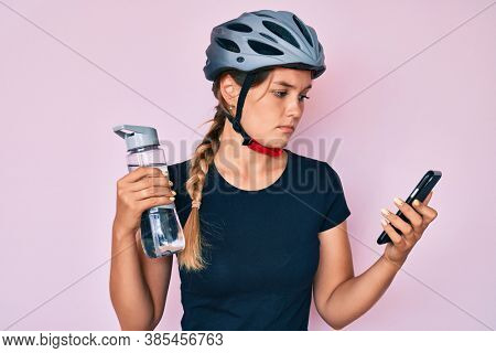 Beautiful caucasian woman wearing bike helmet looking at smartphone relaxed with serious expression on face. simple and natural looking at the camera.