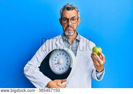 Middle age grey-haired man as nutritionist doctor holding weighing machine and green apple depressed and worry for distress, crying angry and afraid. sad expression.