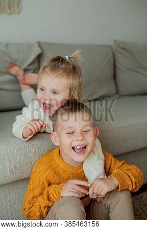 Little Brother And Sister In Cozy Knitted Sweaters Play At Home. Portrait Of Cute Little Brother And