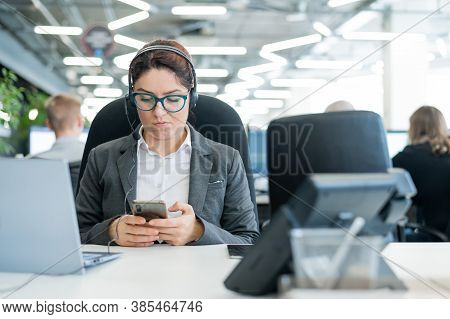 Business Woman Dressed In A Headset Is Bored And Uses A Smartphone While Sitting At A Desk. Female M