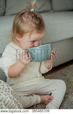 A Little Cute Girl In An Orange Sweater Is Drinking Tea. Cozy Portrait Of A Girlsitting At Home. Fal