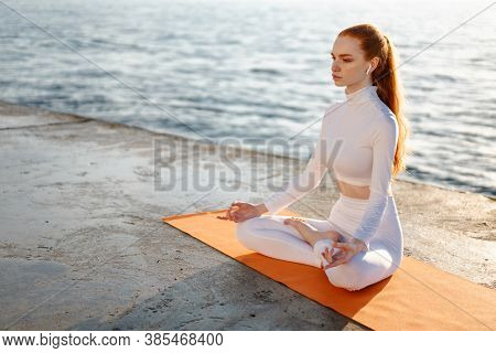Image of redhead calm sportswoman in earphones meditating on promenade at sunrise