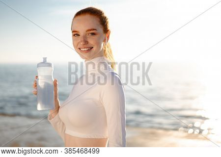 Image of redhead joyful sportswoman in earphones drinking water while working out on promenade