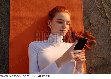 Image of redhead young sportswoman in earphones using cellphone while working out on promenade