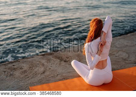 Image of redhead calm sportswoman in earphones doing yoga exercise on promenade at sunrise