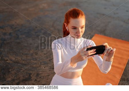 Image of redhead young sportswoman in earphones taking photo on cellphone while working out on promenade
