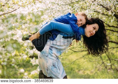 Happy Mother And Son Play And Have A Fun On Sunlit Glade Against Background Of Blooming Spring Garde