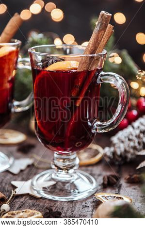 A Glass Of Warming Winter Drink On A Wooden Table Surrounded By New Years Paraphernalia. Festive Moo