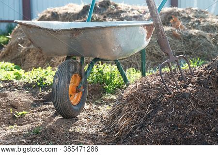 Ecological Organic Fertilizer To Accelerate Plant Growth. Large Pile Of Manure, Pitchfork And Garden