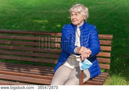 Old Woman With Protective Face Mask On Cane Sits On Bench In Park. Senior Woman Sitting On Bench Out