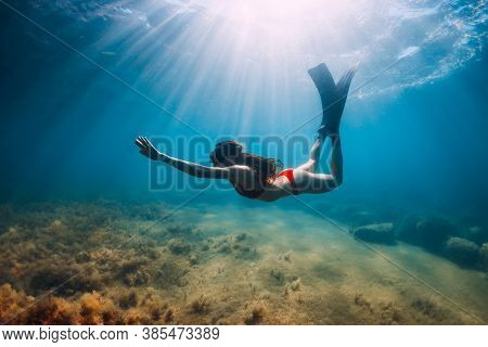 Freediver Slim Woman In Bikini Glides In Blue Sea And Sun Rays. Freediving With Fins Underwater In S