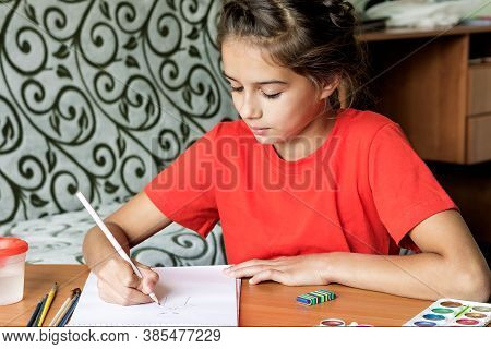 The Girl Sits At Home At The Table Doing Her Favorite Pastime Of Drawing.