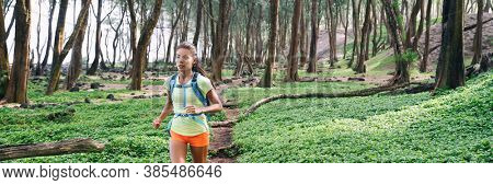 Trail ultra running runner athlete sprinting in forest panoramic. Sport sprinter active Asian girl doing high intensity interval training outdoors in summer banner landscape.