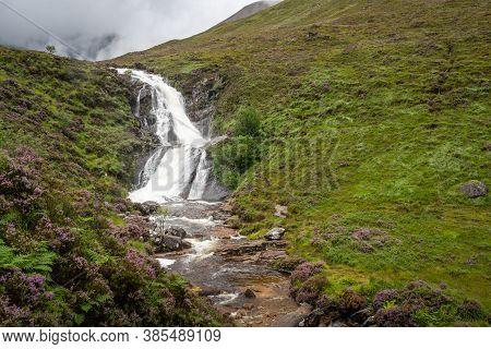 View Of Blackhill Waterfall On Isle Of Skye, Scotland. Blooming Purple Heather Growing Along A Strea