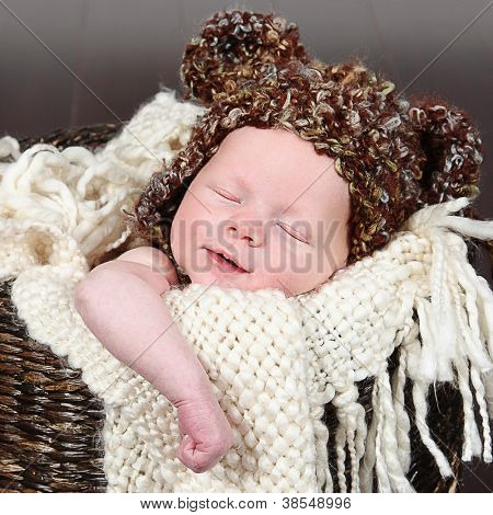 Newborn baby peacefully sleeping with hat on his head