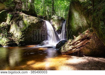 Beautiful Green Forest Landscape With Creek And Waterfall With Slow Shutter Speed And Bright Sunligh