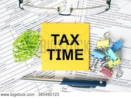 Orange Sticker With Text Tax Time. Colored Stationery Clips, Green Paper Clips And Eyeglasses