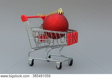 Close-up Of A Red Christmas Ball Lies In A Shopping Cart. The Concept Is A Postcard, A Holiday Invit
