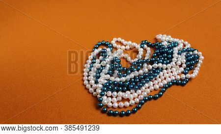 Two Pearl Necklaces On A Yellow Background. One Necklace From White Natural Pearls, The Second From