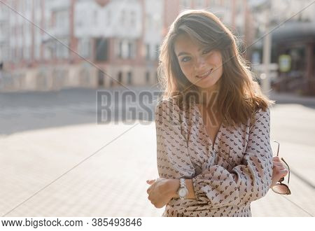 Side View Backlight Portrait Of A Woman Smiling And Looking To The Camera, Outside In The Evening