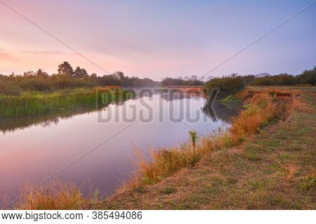 River Misty Autumn Sunrise. Colorful Dawn. Cloudy Sunrise.