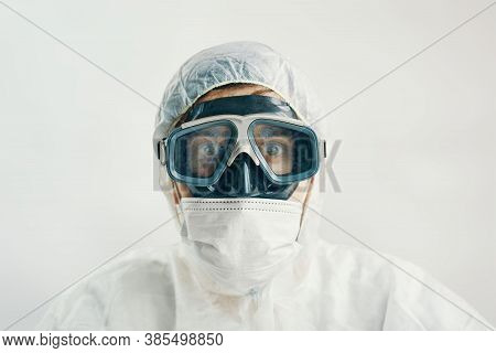 Virologist In A Protective Suit With A Scared Look On A White Background. Male Professional In Hoode